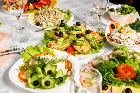 table lined with variety of dishes from which the centerpiece is dish with several tartlets with chicken, ham, cucumbers, lettuce and olive.