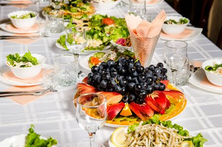 table lined with variety of dishes from which the centerpiece is dish with sliced fruit.
