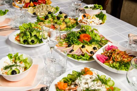 table lined with variety of dishes from which the centerpiece is dish with banquet cutting with ham and dish with several tartlets with chicken and ham. Stockfoto