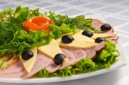 banquet cutting with ham, meat delicacies, cheese, sausage smoked, olive, lettuce and tomato on white dish. Фото со стока