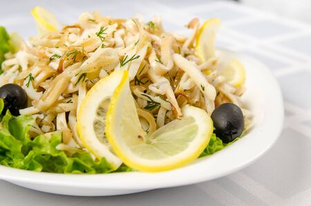fried squid with onions and lettuce, garnished with lemon and olives.