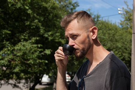 young bearded man drinking coffee on a background of trees on a sunny summer day.