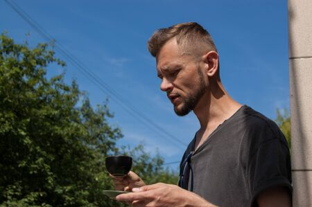 young bearded man with a cup of coffee in his hand against the blue sky on a sunny summer day.