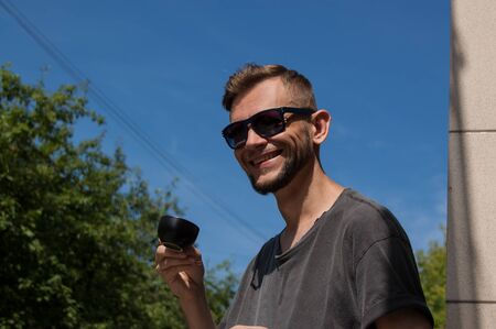 smiling bearded man with cup of coffee in his hand against the blue sky on sunny summer day.