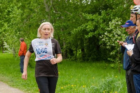 Komsomolsk-on-Amur, RUSSIA - JUNE 2, 2019. Running competitions among elderly sports veterans. elderly woman runs on the track at running competition among senior athleties Publikacyjne