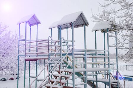 playground with slide under the snow.