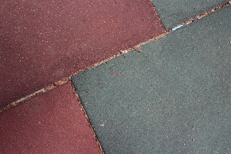 burgundy and gray artificial turf tiles at a children's playground placed at an angle.