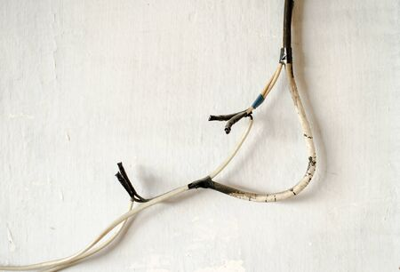 electrical wires temporarily connected by hand and insulated with electrical tape against a white wall.