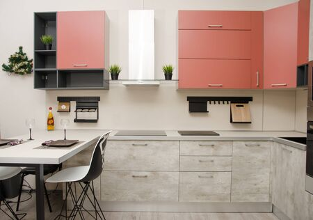 modern loft style kitchen with hob, fume hood and table with countertop.