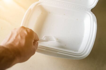 male hand with a white plastic fork and an empty foam container for food.