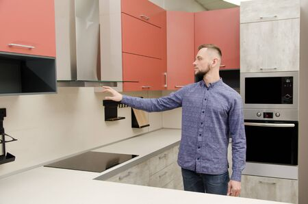 Attractive bearded man checks the inclusion of a fume hood in a modern kitchen.