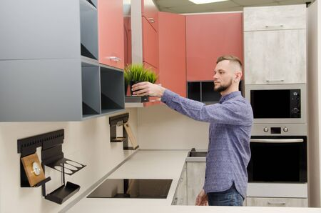 attractive bearded man puts a decorative pot with artificial grass on a fume hood in a modern kitchen. Banque d'images