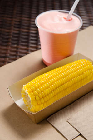 an ear of boiled corn in an eco-friendly cardboard box next to a milkshake.