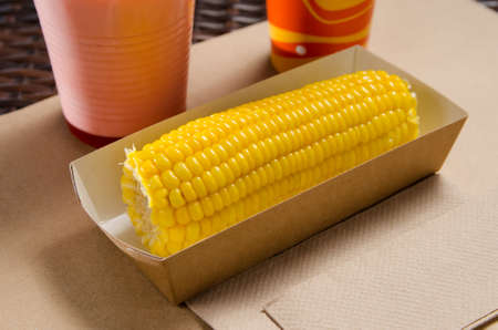 an ear of boiled corn in an eco-friendly cardboard box next to a milkshake and popcorn.