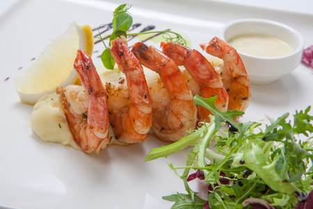 cebollines: Fried shrimps with mashed potatoes with sauce on a white plate garnished with fresh lettuce