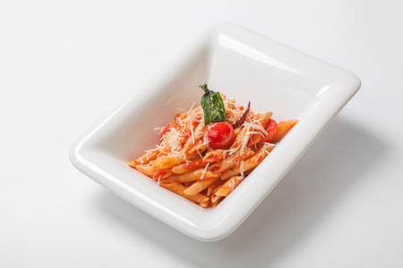 Pasta with spicy tomato sauce and basilicum sprinkled with Parmesan cheese