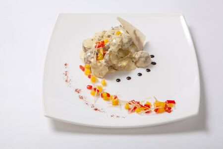 haricot: Baked in their skins potatoes with a creamy sauce. Baked young potatoes with cream sauce decorated with cubes of fresh sweet pepper on a white plate
