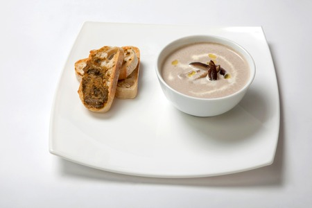 Cream soup from mushrooms in a deep white dish with slices of bread