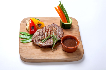 Beef grilled medium rare on a wooden Board with a side dish of mashed potatoes and sweet peppers on the grill, served additional sauce, decorated with pods of young peas, and strips of fresh carrots