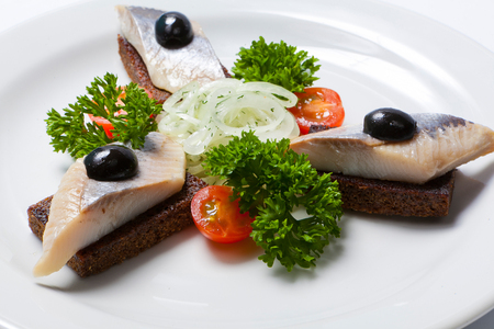 Sliced black bread and herring and fresh onion on a white plate