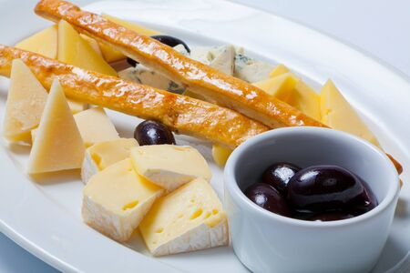 tabla de quesos: various types of cheese and olives on a white plate