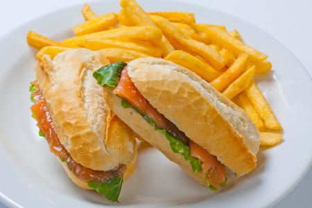 Sandwich met zalm, tomaat, kaas en gouden frietenaardappels op een plaat