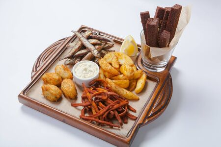 onion rings: Fresh beer snacks assortment on wooden board. Isolated image Stock Photo