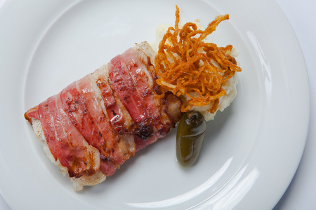 stockfish: Baked cod wrapped in bacon and mashed poatoes with pickles on a white plate
