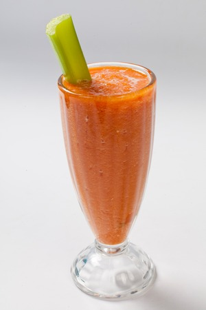 cold carrot smoothie with celery in the glass. White background. Isolated