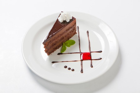 Chocolate cake with chocolate creame and meant on a white plate