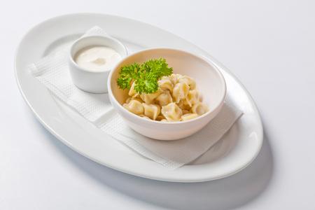 Meat dumplings - russian pelmeni, ravioli with meat in a deep bowl. Close up
