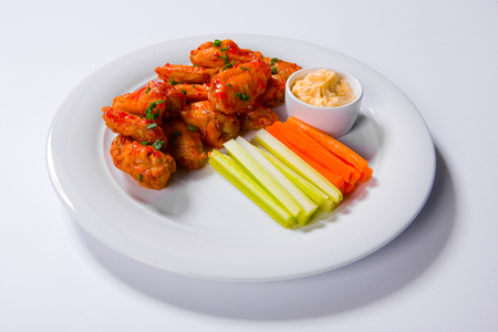 buffalo chicken wings sitting on plate garnished with carrot and celery sticks with blue cheese dipping sauce