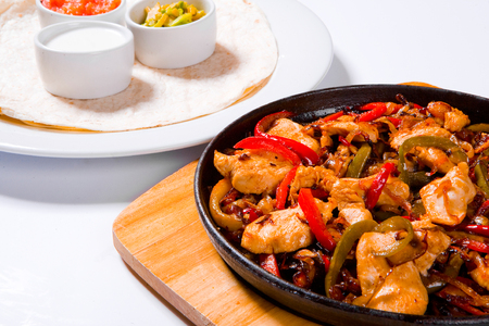 Stir fry chicken with sweet peppers and green beans in wok pan close-up Stock Photo