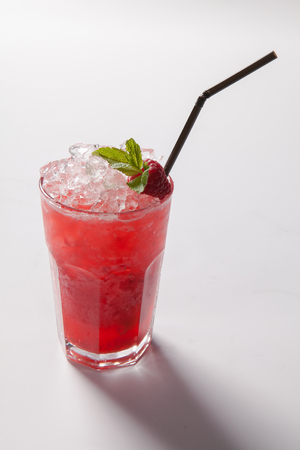Cold straw red drink with berry and mint leaf. Isolated