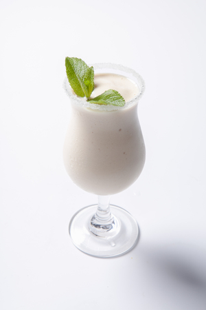 Delicious milkshake with a leaf of mint on top on a white background. Isolated