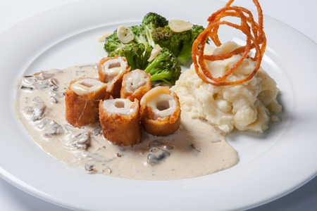 Chicken Cordon bleu on a plate with rustic mashed potatoes. Close up
