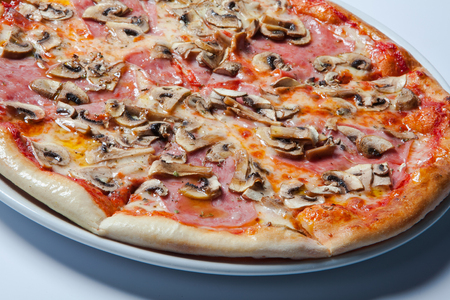 Italian delicious pizza with mushrooms and ham. White background Stock Photo