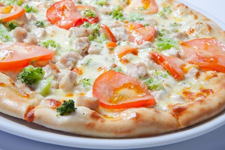 Italian delicious pizza with tomato, broccoli and cheese. White background Stock Photo
