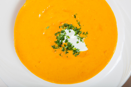 Homemade pumpkin soup with cream with spices on white plate. Close up