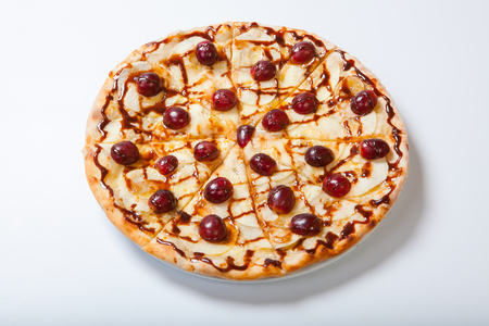 sweet apple pizza with sliced grape on white background. Close up