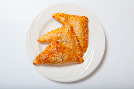danish: Homemade cheese puff pastries on a white plate. White background