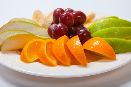 Plate of sliced ripe fruit on a white background. Close up