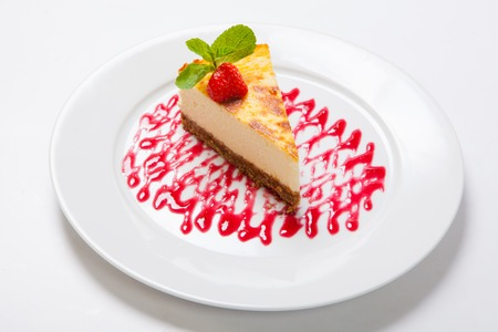 Cheesecake with fresh strawberries on white plate. Close up