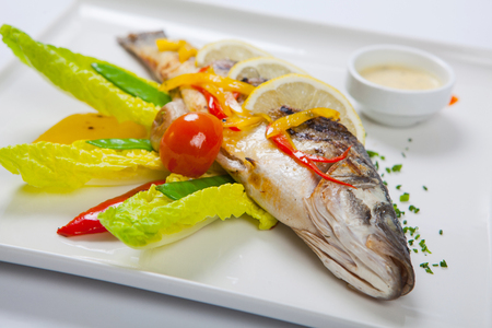 flesh eating animal: Grilled whole fish decorated with leaves of lettuce and cherry tomato, served with garlic sauce. Fried whole fish closeup Stock Photo