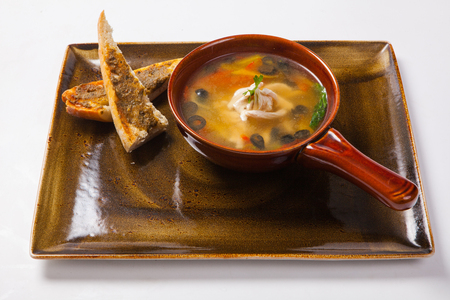 chicken soup and bread on a white background