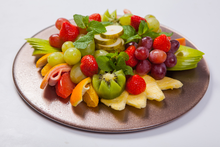 kiwi fruta: Mixed Fruit platter with assorted fruits on a white background.
