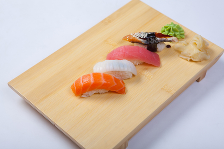 Sushi with salmon on a wooden tray. White background