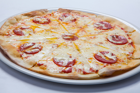Tasty pizza with salami on white plate. White background.
