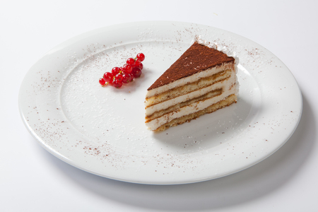 tiramisu on a white plate decorated with red currants.