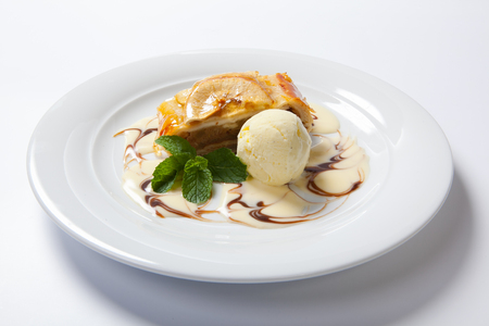 Apple strudel with vanilla ice cream on a white background Stock Photo